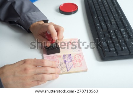 Immigration control officer will arrival stamp in the passport - stock photo