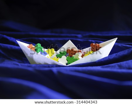 Immigration emigration migration conceptualization, white paper boat full of colorful meeples, refugee crisis topic illustration and social issues symbol