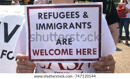 "Immigration Supporter Holding A Sign That Says ""Refugees and Immigrants are Welcome Here"""