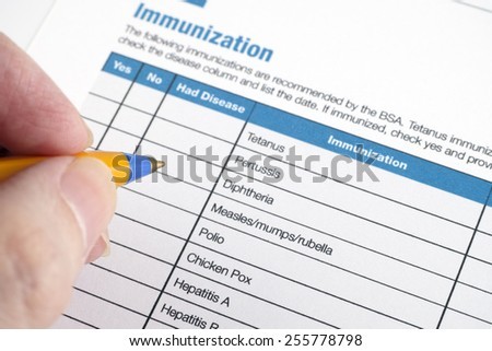 Immunization application form and human hand with ballpoint pen.  - stock photo