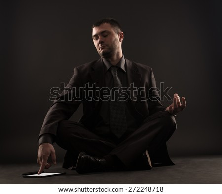 Impatient businessman can not meditate because he looking at the tablet  - stock photo