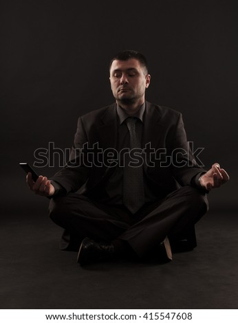 Impatient businessman unable to meditate because his attention is refocused on the phone.