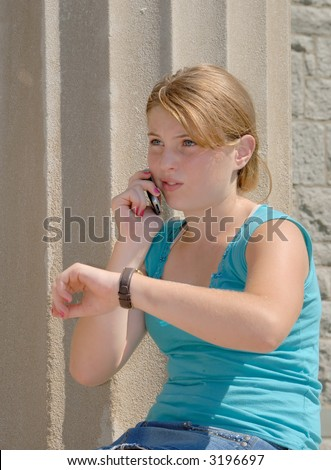 Impatient girl, sitting outside, looking at her watch and talking on her cell phone - stock photo