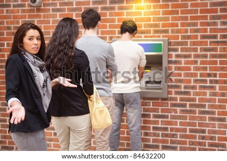 Impatient woman queuing at an ATM - stock photo