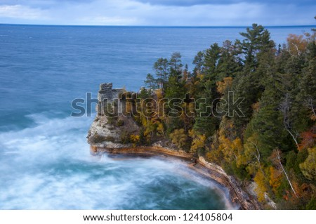 Impending storm on rocky shoreline by autumnal forest - stock photo