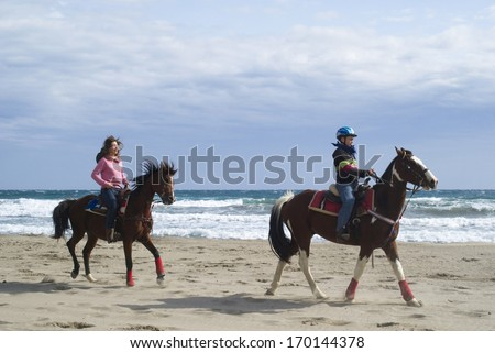 IMPERIA, ITALY - OCTOBER 10: Unidentified teens riding horses on the beach at Imperia in Italy on October 10, 2010