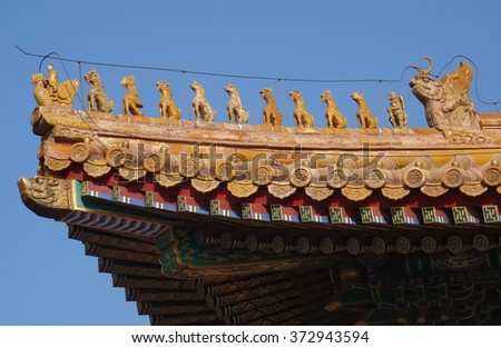 Imperial roof decoration on the Temple of Supreme Heaven, Forbidden city, Beijing, China. Highest possible status roof charms- man riding bird, nine beasts, immortal figure, and dragon. - stock photo