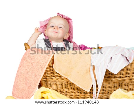 Impish little baby with a cute little self-satisfied expression sitting in amongst the washing in a wicker laundry basket - stock photo