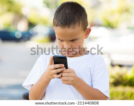 Important Text Message. Portrait Teenage boy looking concerned with text message on his phone, isolated outdoor street background. Human face expressions, emotions, body language, reaction, feelings - stock photo