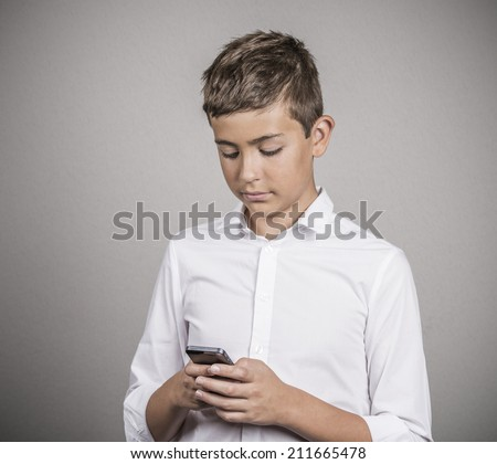 Important Text Message. Portrait Teenage boy looking on screen, reading text message on his phone, isolated grey wall background. Human face expressions, emotions, body language, reaction, feelings - stock photo