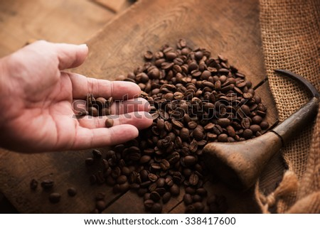 Imported coffee beans spilling out from a hemp sack, on wooden crate lid. Inspecting imported coffee beans. Focus is on the coffee beans. Shallow depth of field.  - stock photo