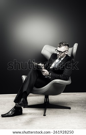 Imposing mature man in elegant suit sitting on a leather chair in a modern luxurious interior and working on a laptop. Fashion. Business. Black-and-white portrait. - stock photo
