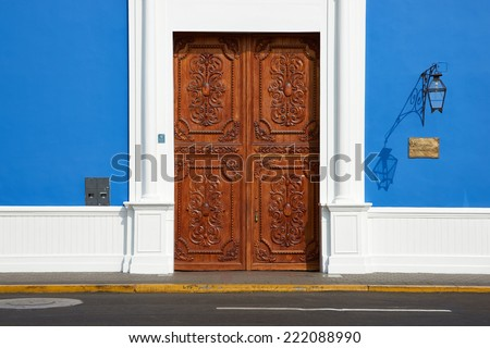 Imposing wooden door to bright blue and white Spanish colonial style building in the Plaza de Armas in the centre of Trujillo in northern Peru. - stock photo