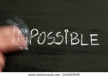 Impossible replaced by possible message isolated on black background, with moving hand erasing IM letters.Chalk drawing on blackboard. Business Concept image. - stock photo