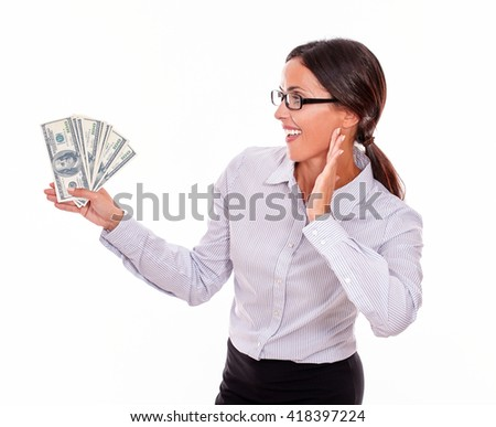 Impressed brunette businesswoman holding dollar bills with an excited gesture of one hand and smiling while looking at money in a button down shirt and her hair tied back on a white background - stock photo
