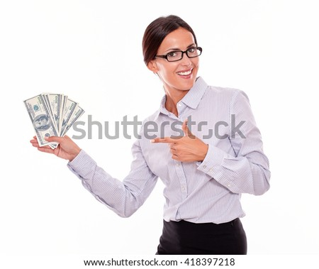 Impressed brunette businesswoman holding dollar bills with an excited gesture pointing at the money while smiling and looking at the camera wearing a button down shirt and her hair tied back, isolated