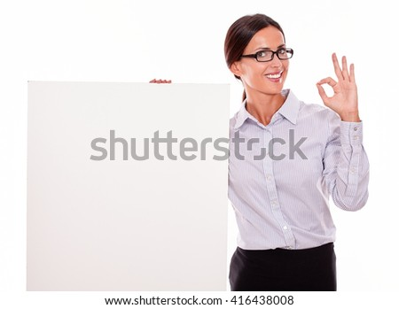 Impressed brunette businesswoman looking at the camera, holding a placard smiling, wearing her straight hair tied back and a button down shirt, with a gesture of her left hand a perfect sign - stock photo