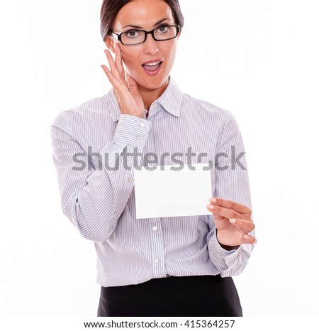 Impressed brunette businesswoman with glasses, wearing her long hair tied back, and a button down shirt, holding a blank copy space in one hand and touching her glasses with the other hand