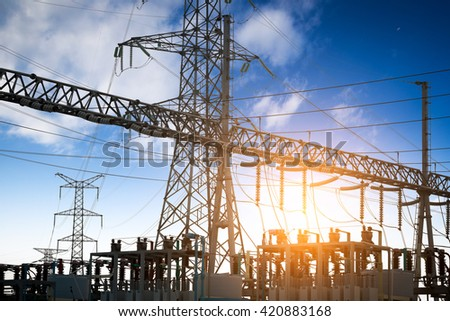 Impression network at transformer station in sunrise, high voltage up to yellow sky take with yellow tone, horizontal frame