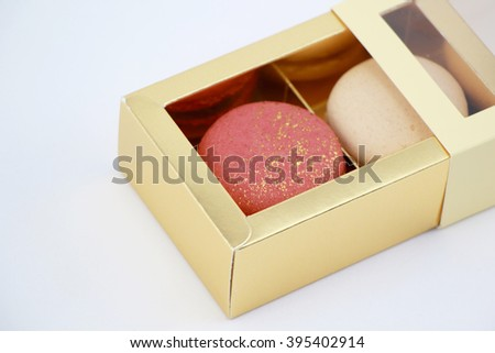 Impressive a gold-red and A pearly white, large-sized patterned macaron filled with mild sweet lychee ganache , raspberry jelly and chocolate packaged in a box - stock photo