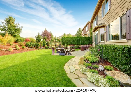 Impressive backyard landscape design with cozy patio area - stock photo