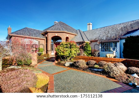 Impressive luxury house with colomn porch, tile roof, stoned walkway. Winter, snowy day. - stock photo