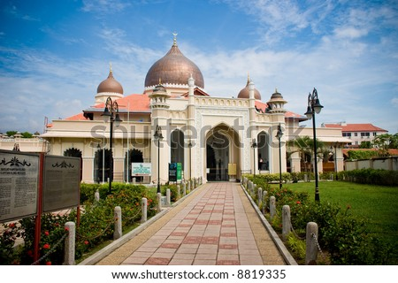 impressive mosque architecture with front bricks walk way, blue sky white clouds - stock photo
