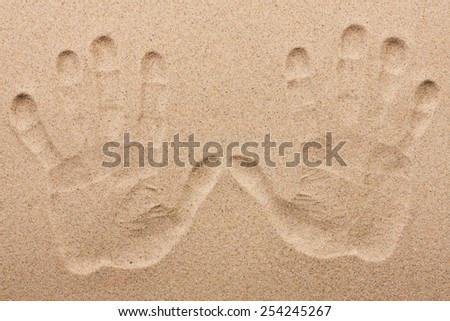 Imprint of two human hands in the sand, as background