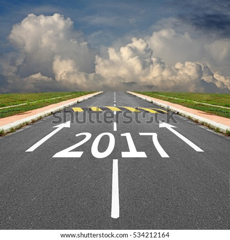 Imprint of Year 2017 and arrow on an asphalt road with speed bump against a surreal dramatic cloudy sky, for the concept: Slow down as we approach New Year 2017.