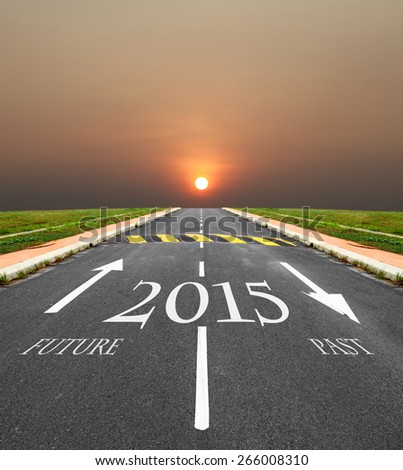 Imprint of Year 2015 and directional arrow of the future and past on an tarmac road vanishing into the horizon with a fiery setting sun. - stock photo