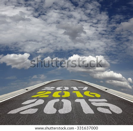 Imprint of Year 2015, 2016 and 2017 timeline on an tarmac road vanishing into the horizon of a blue cloudy sky. - stock photo