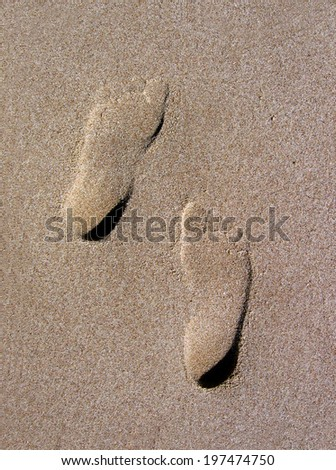 Imprints of two feet in the desert sand.  - stock photo