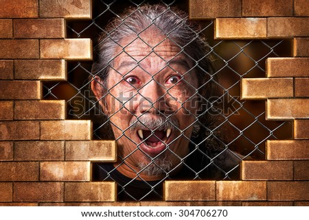 Imprison old man vampire internal the metal grate bar and brick wall in concept of detain the wicked evil - stock photo