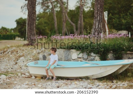 in a forest on the banks of a little boy sitting on the boat and looks into the distance - stock photo