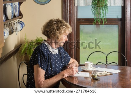 In a historical scene from the 1930??s or 1940??s, an attractive elderly woman writes a letter as she sits at a table by a window. - stock photo