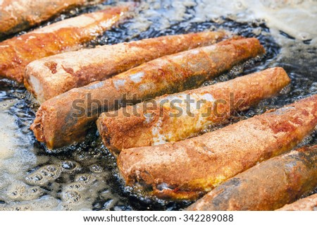 In a large pan lie next to each other some fried in bread crumbs fishes with some steam around