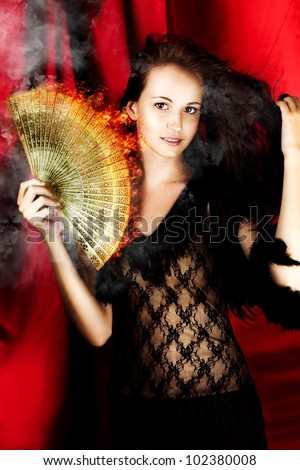 In A Show Of Smoke And Flames A Hot Woman Theatre Performer Dances On A Broadway Stage With A Flame Fan, In A Image Titled Hot Female Fire Dancer - stock photo