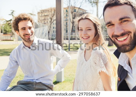 In a sunny spring, a group of three young friends, two men and a woman are sitting on a park bench talking and joking