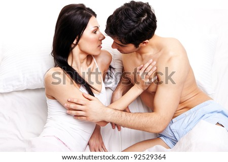 In Anticipation Of A Kiss. Loving couple poised to kiss in bed, studio portrait on white - stock photo