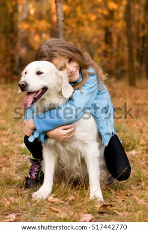 In autumn forest meadow preaty little girl hug her golden retriever in the autumn forest. submissiveness