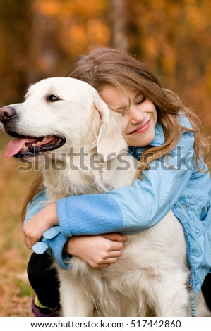 In autumn forest meadow preaty little girl with her golden retriever in the autumn forest. submissiveness