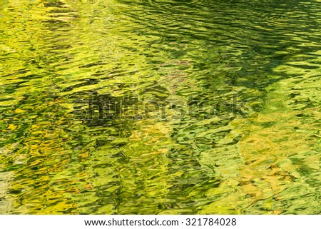 In Autumn sunshine the light on the trees reflects green and yellow on the river Usk - Brecon Beacons. September - stock photo