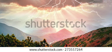 In autumn the mountains are shrouded in thick fog that barely shine through Sun ... Blueberries- bright red coniferous forest green orange buk- mountains sinie- fantastic charm.Rays through the storm  - stock photo