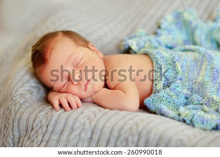 in bed sleeping baby in a blue cap with a large bubo