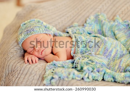 in bed sleeping baby in a blue cap with a large bubo - stock photo