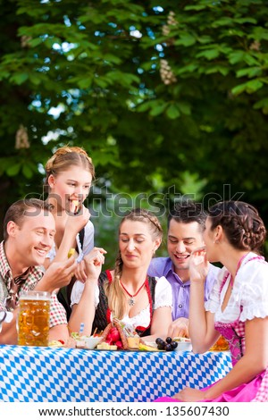 In Beer garden - friends Tracht, Dirndl and on a table with beer and snacks in Bavaria, Germany - stock photo