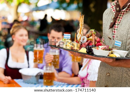 In Beer garden in Bavaria, Germany - beer and snacks are served, focus on meal - stock photo