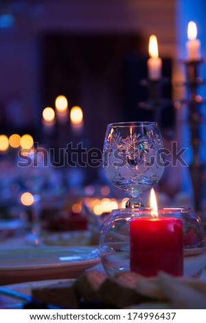 In blue light holiday table with candles and a glass