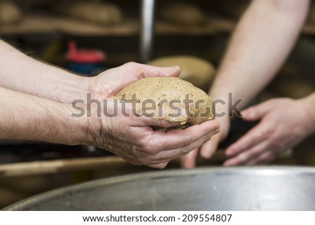 In bread bakery, food factory, manual workshop, people working together making handmade bread