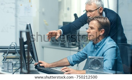 In Busy Engineering Bureau Two Senior Engineers Discussing Technical Issues over Personal Computer. Their Office Looks Minimalistic and Modern.